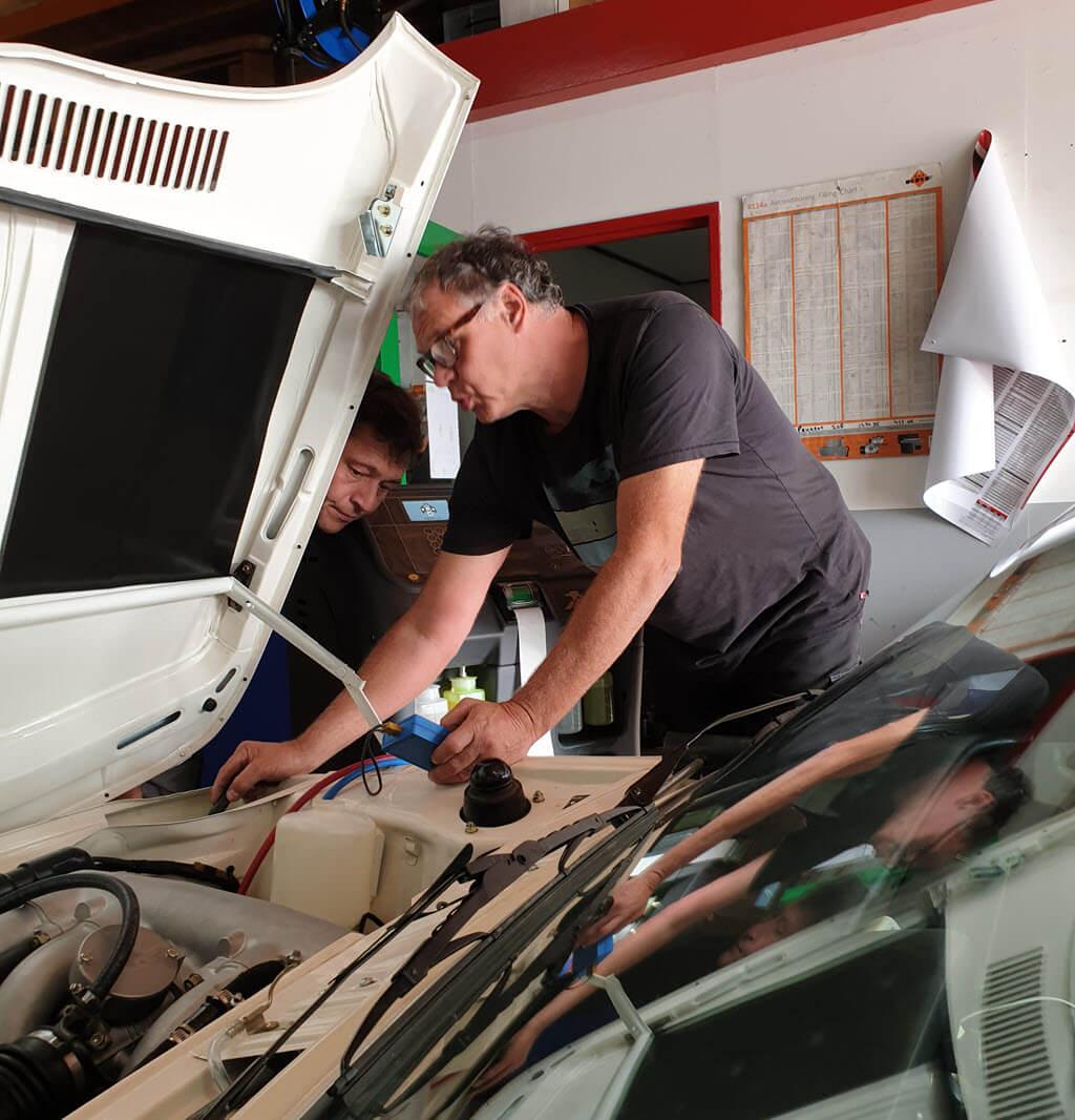 Frans en Lucien controleren en meten de temperatuur van de ingaande en uitgaande leiding